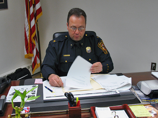 Police officer sitting at desk with papers.