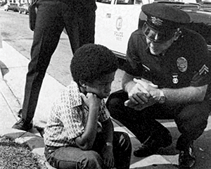 Officer kneeling down to talk to child.
