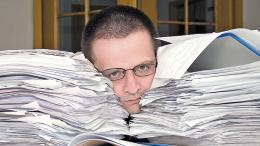 Man's head buried in paperwork