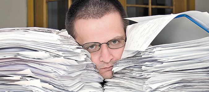 Man's head buried in paperwork
