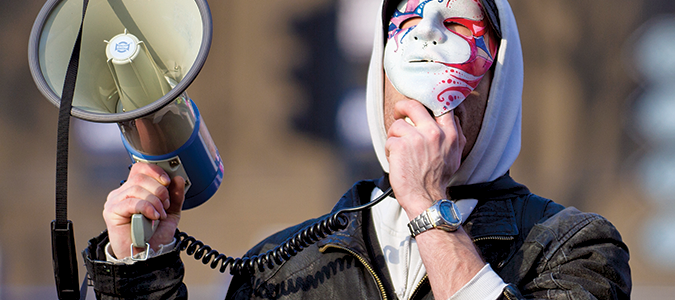 Man with bullhorn wearing a mask.
