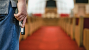 Hand holding a pistol inside a church.