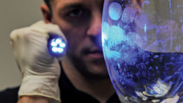 A man is looking at fingerprints on a glass vase.