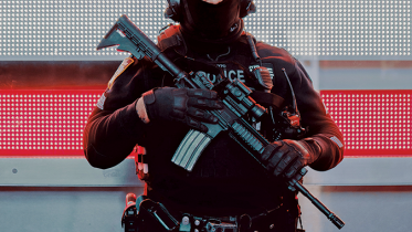 Police officer in uniform holding weapon.