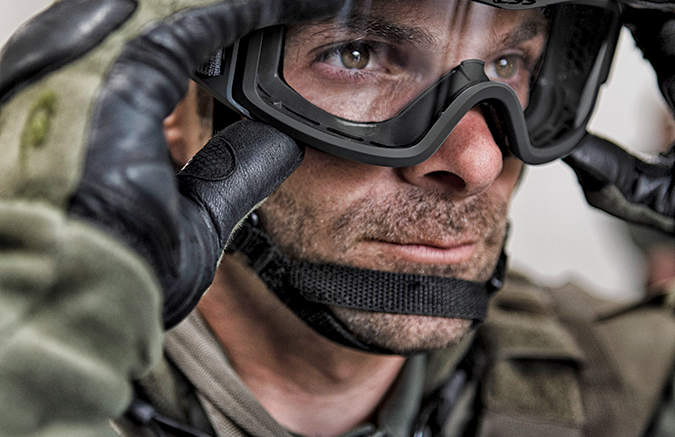 Man in uniform putting on goggles.
